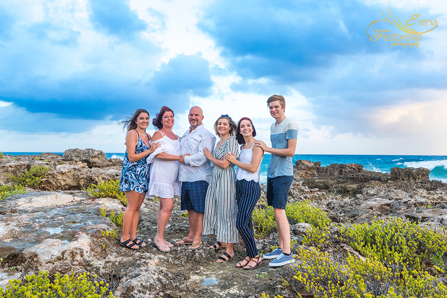family photo standing on rocks